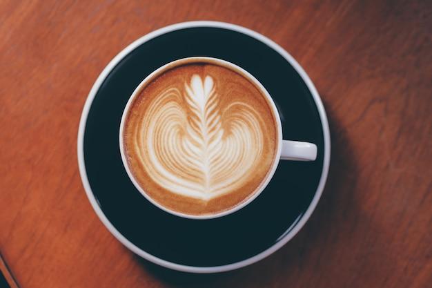 Bliska ręka barista przy filiżance kawy.