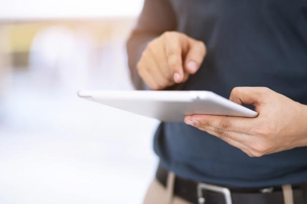 Bliska ręka biznes człowiek pracujący przy użyciu cyfrowego tabletu pc stojąc przed w biurowcu z widokiem na miasto.