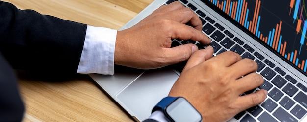 Bliska ręka biznesmena handlującego akcjami handlowymi i szukanie danych wykresu finansowego biznesu na laptopie
