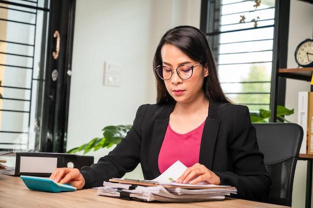Bliska ręka businesswoman za pomocą kalkulatora finansów gospodarstwa domowego lub podatków na maszynie, koncepcji finansów i rachunkowości,