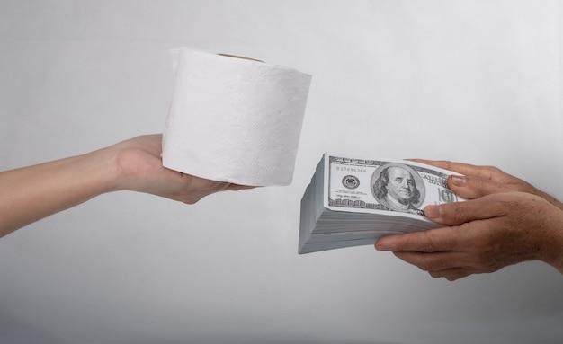 Bliska ręka chusteczki sellbuy trzyma papier toaletowy i pieniądze banknotów 100 usd