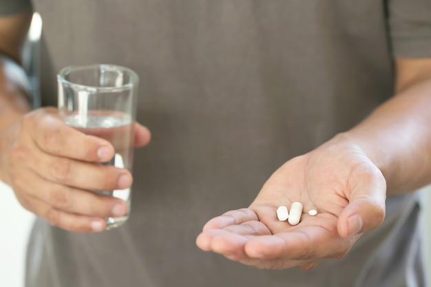 Bliska ręka człowieka biorąc wiele tabletek weź lek w ręku trzymając szklankę wody pitnej.