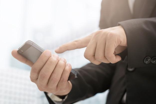 Bliska ręka człowieka biznesu za pomocą inteligentnego telefonu komórkowego tekstowego