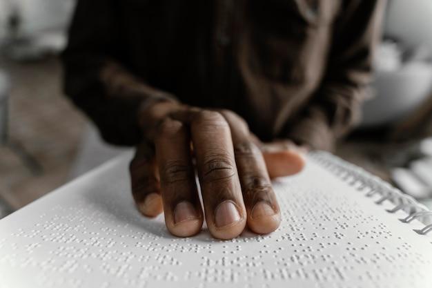 Bliska ręka czytająca alfabet braille'a