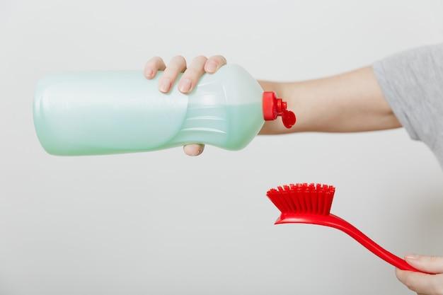 Bliska ręka gospodyni nalewa płyn do mycia naczyń na czerwony pędzel do mycia naczyń na białym tle. kobieta trzyma butelkę z płynem czyszczącym