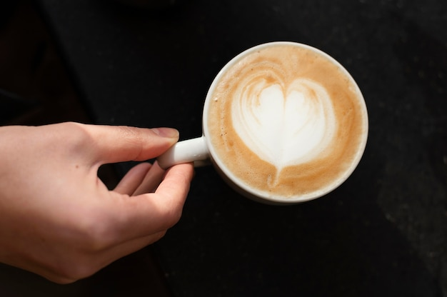 Bliska ręka i filiżanka kawy