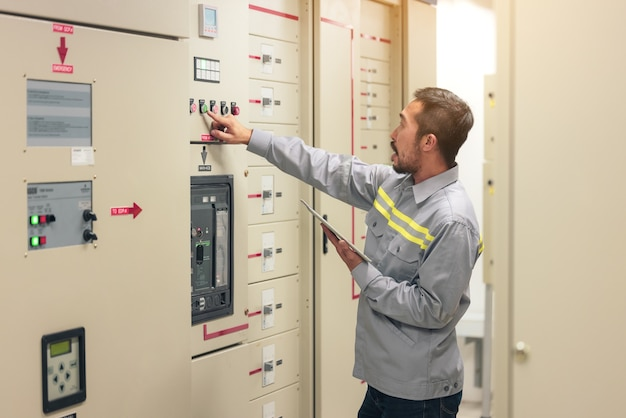 Bliska ręka inżyniera lub elektryka pracującego człowieka sprawdzić układ elektryczny za pomocą tabletu w fabryce.