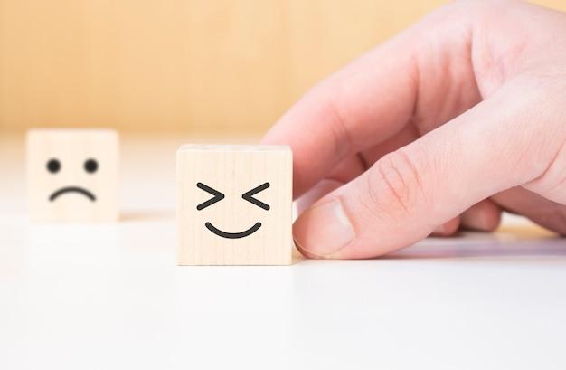 Bliska ręka klienta wybierz buźkę i niewyraźne smutną twarz ikona na kostce drewna, ocena usługi, pojęcie satysfakcji.