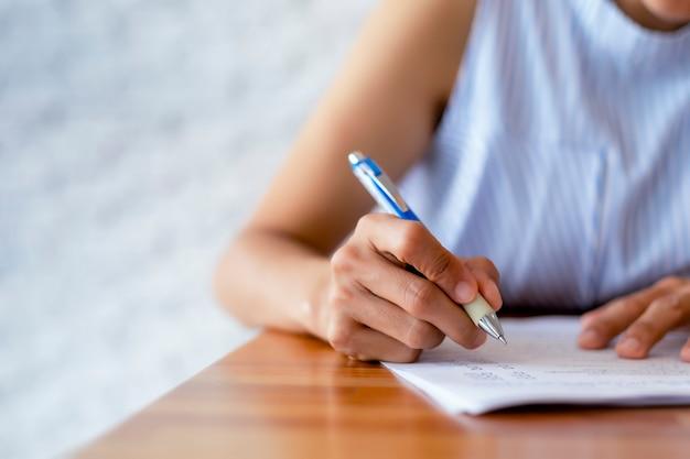 Bliska ręka kobiet biznesu używa papieru do pisania długopisem