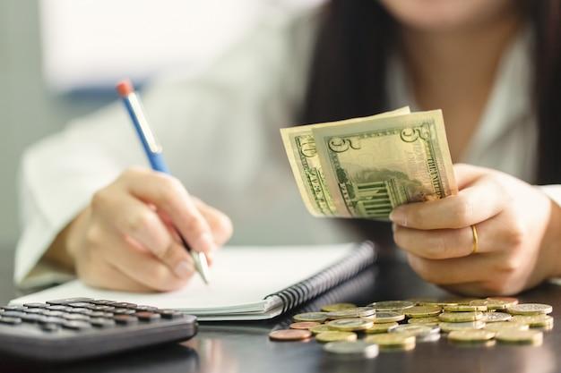 Bliska ręka kobieta z ołówkiem pisania na książki i trzymać rękę dolara. obliczanie w domu