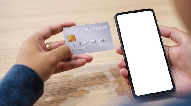 Bliska ręka kobiety robiąca zakupy online za pomocą karty kredytowej za pomocą inteligentnego telefonu w kawiarni