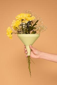 Bliska ręka kobiety z plastikowym lejem z kwiatami