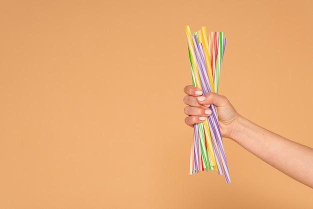 Bliska ręka kobiety z plastikowymi słomkami