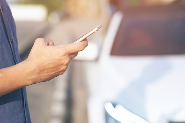 Bliska ręka ludzie ludzie stoją za pomocą inteligentnego telefonu komórkowego na poboczu drogi. zadzwoń do mechanika samochodowego poproś o pomoc, ponieważ samochód jest uszkodzony.