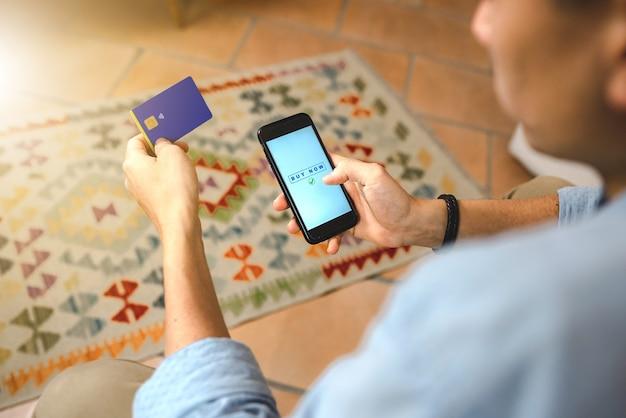 Bliska ręka mężczyzny robi zakupy online ze smartfonem siedząc na kanapie. płatność internetowa kartą kredytową. koncepcja bankowości domowej i technologii.