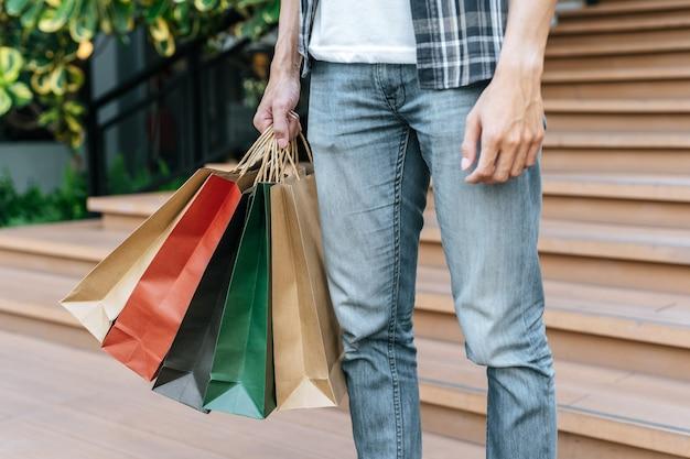 Bliska ręka mężczyzny trzymającego wielokrotną torbę na zakupy