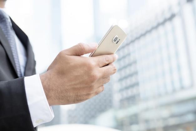 Bliska ręka młodego człowieka za pomocą inteligentnego telefonu komórkowego.