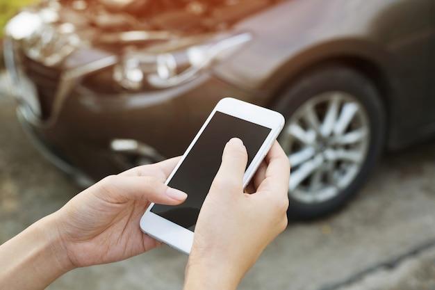 Bliska ręka młody biznesmen za pomocą smartfona zadzwonić do mechanika samochodowego poprosić o pomoc