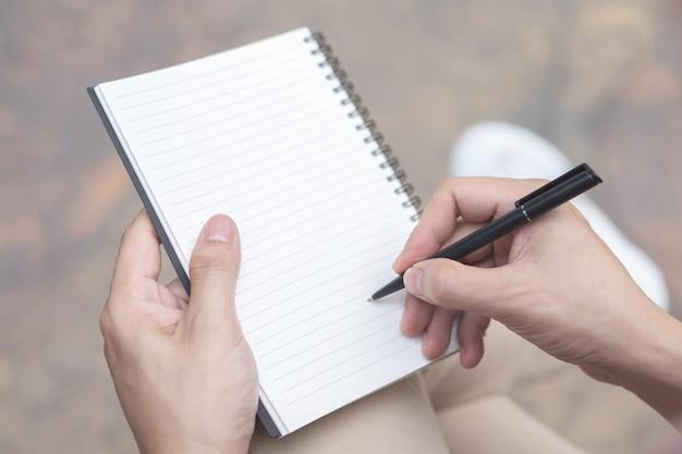 Bliska ręka młody człowiek używa pisania piórem notatnik wykład zapisu do książki siedzącej na krześle na świeżym powietrzu.