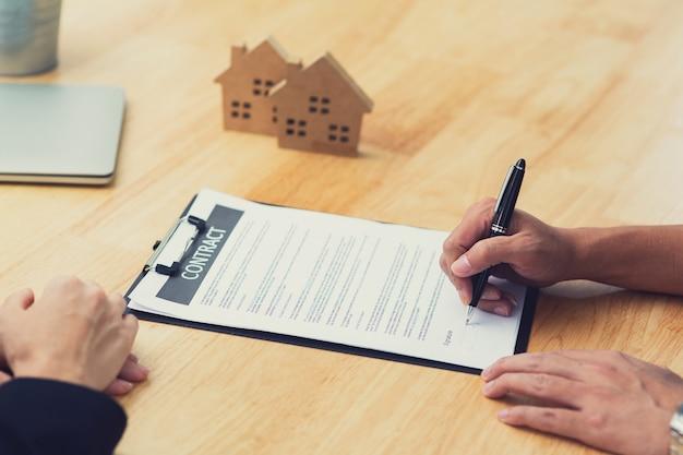 Bliska ręka podpisuje podpis na papierze kontraktowym domu z agencją sprzedaży domu nieruchomości