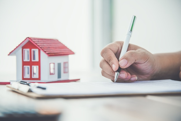 Bliska ręka podpisywania dokumentu pożyczki podpis na własność domu. inwestycja hipoteczna i nieruchomości, ubezpieczenie domu, ochrona