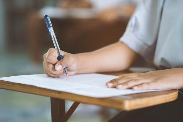 Bliska ręka studenta czytania i pisania egzamin ze stresem w klasie