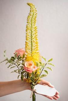 Bliska ręka trzyma bukiet kwiatów