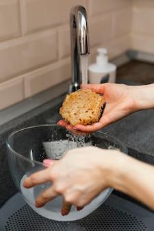Bliska ręka trzyma gąbkę do czyszczenia