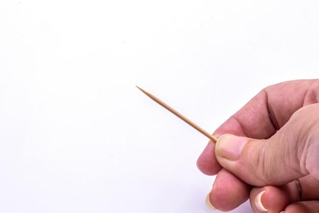Bliska ręka trzyma izolat drewniana wykałaczka.