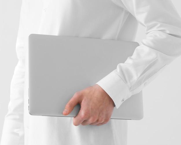 Bliska ręka trzyma laptopa
