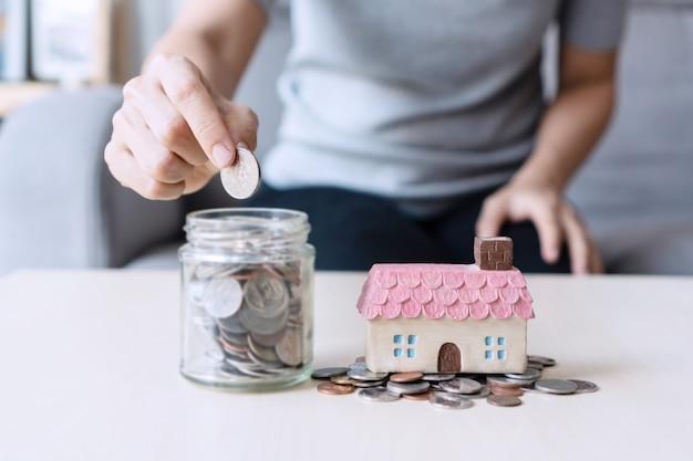 Bliska ręka trzyma monetę, stos pieniędzy i dom zabawki na stole, oszczędzając na przyszłą koncepcję.