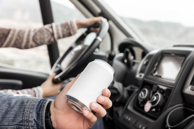 Bliska ręka trzyma puszkę sodową w samochodzie