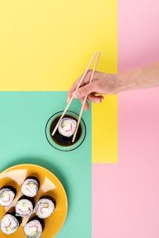 Bliska ręka trzyma sushi pałeczkami
