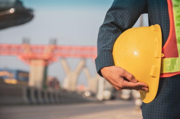 Bliska ręka trzyma twardy kapelusz tło budowy witryny, kask ochrony inżyniera architektury