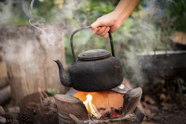 Bliska ręka trzyma zagotować wodę stary czajnik na ogniu z piecem na węgiel drzewny na niewyraźne tło