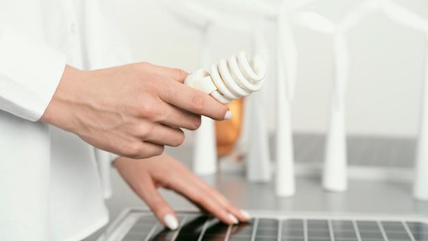 Bliska ręka trzyma żarówkę eco