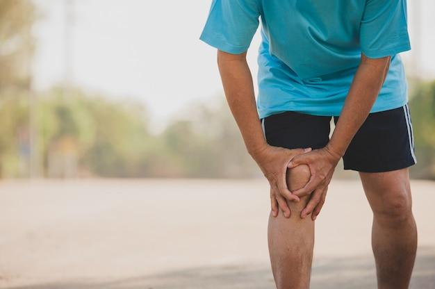 Bliska ręka trzymać kolano, starszy mężczyzna to ból kolana