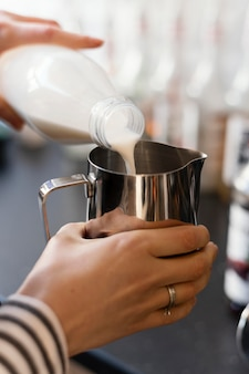 Bliska ręka wlewając mleko do filiżanki
