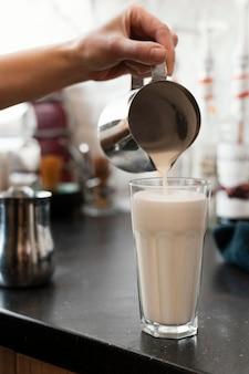 Bliska ręka wlewając smaczne mleko w szklance