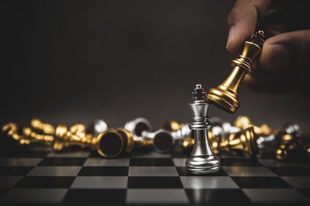 Bliska ręka wybrać złote szachy do walki ze srebrną drużyną szachową na szachownicy