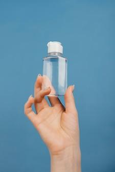Bliska ręka z butelką do dezynfekcji rąk