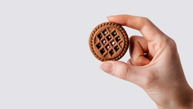 Bliska ręka z czekoladowym ciastkiem