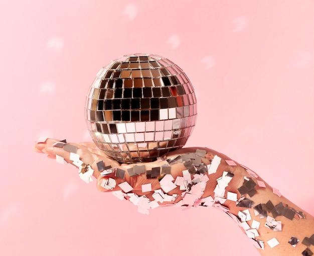Bliska ręka z disco globe i brokatem