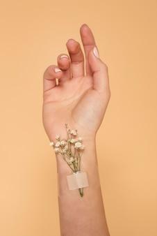 Bliska ręka z pomocą zespołu i kwiatami