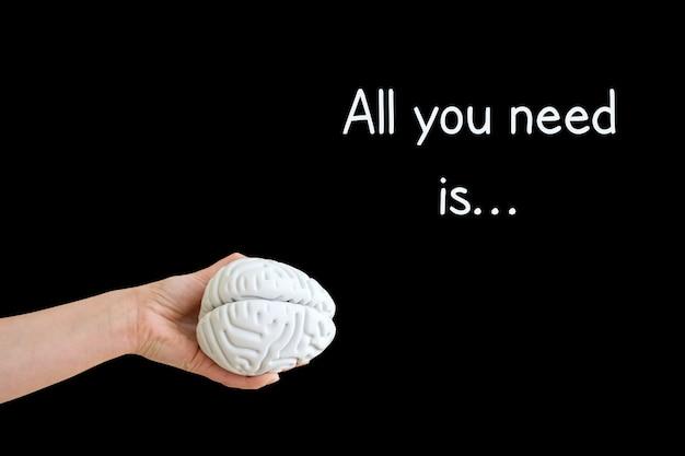 Bliska ręki trzymającej mózg na czarnym tle napis