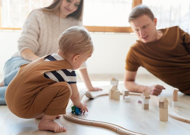 Bliska rodzice bawią się z małym dzieckiem