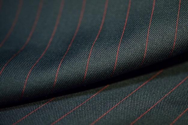 Bliska roli ciemny szary materiał garnitur z czerwoną linią taśmy, photoshoot przez głębia ostrości dla obiektu