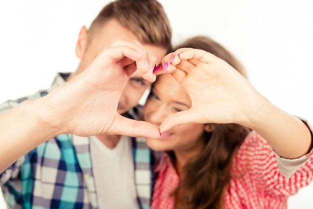 Bliska romantyczna para zakochanych, wskazując na serce palcami