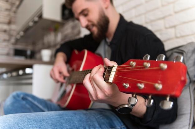 Bliska rozmazany mężczyzna gra na gitarze