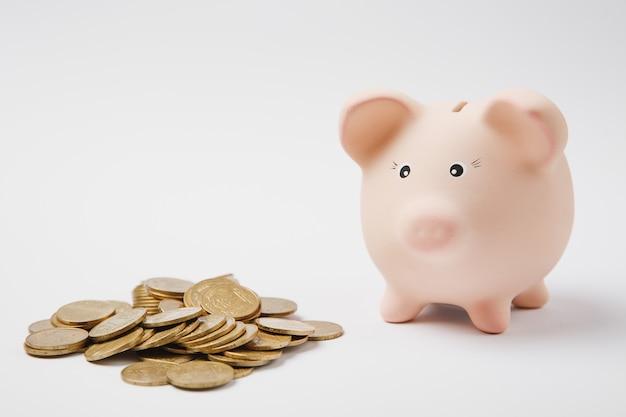 Bliska różowy piggy bank pieniędzy, stos złotych monet na białym tle na tle białej ściany. akumulacja pieniędzy, inwestycje, usługi bankowe lub biznesowe, koncepcja bogactwa. skopiuj makiety reklamowe.